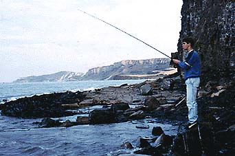 An angler backed up against cliffs by a big spring tide.